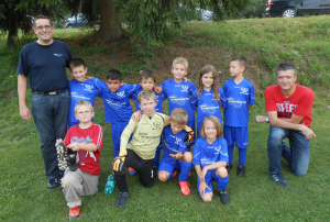 Im Bild: Trainer Carsten Jungmann (rechts) mit Manfred Spindler (links) und den F-Jugendlichen mit den neuen Trikots der Fa. Spindler Verzahnungstechnik